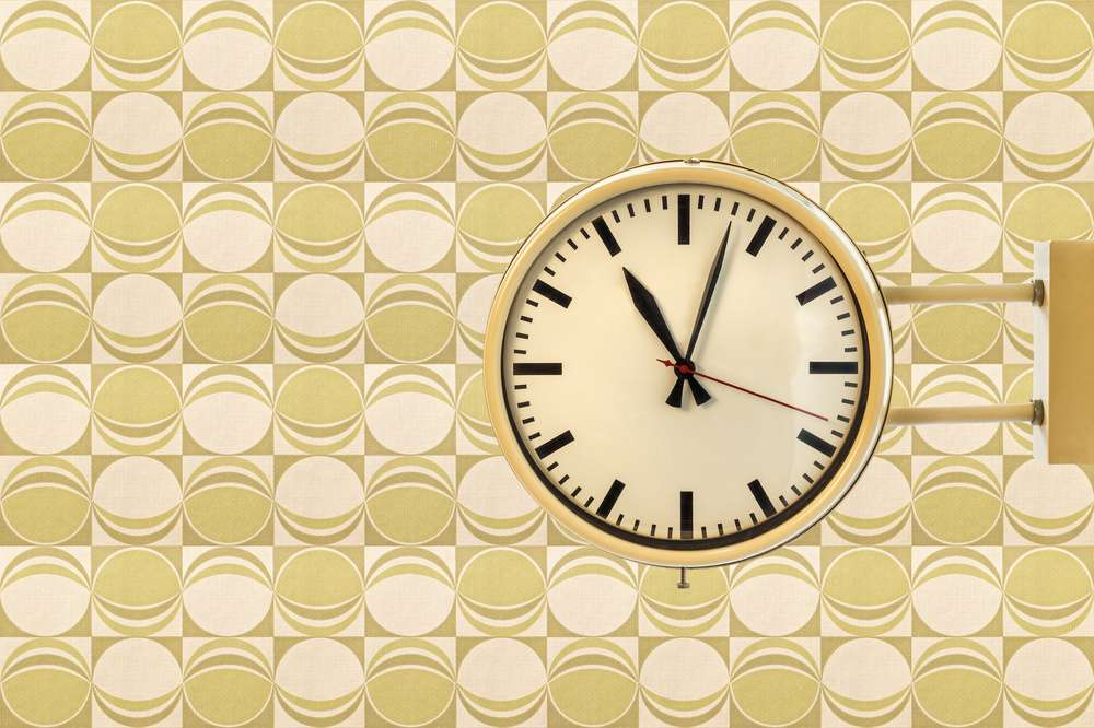 Seventies vintage office clock against a retro wallpaper background
