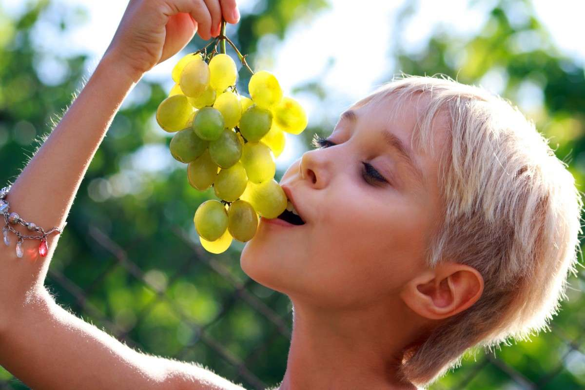 blonde girl eats grapes