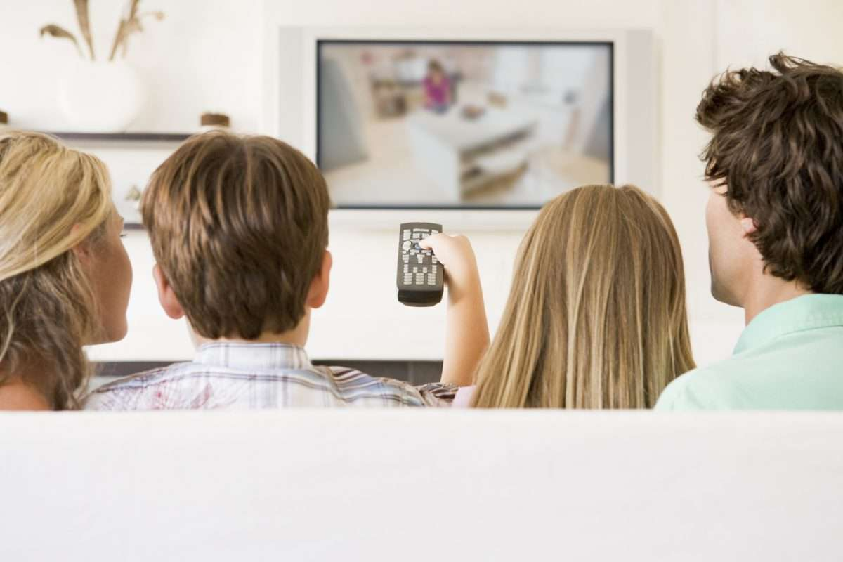 Family in living room with remote control and flat screen televi