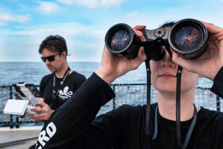 Spotter Using Binoculars to Scan the Horizon