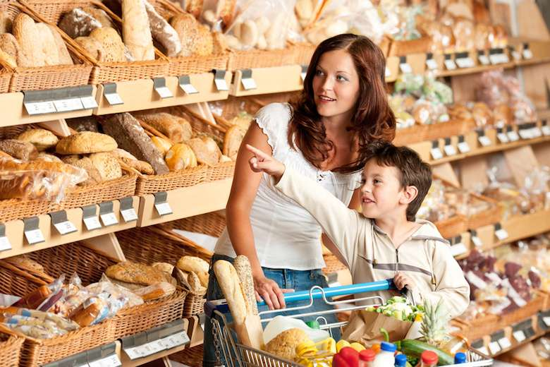 Grocery store shopping - Woman with child in a supermarket choosing bread