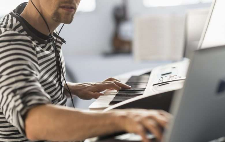 Man Using Laptop and Synthesizer