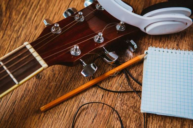 Headphones with guitar notebook and pencil