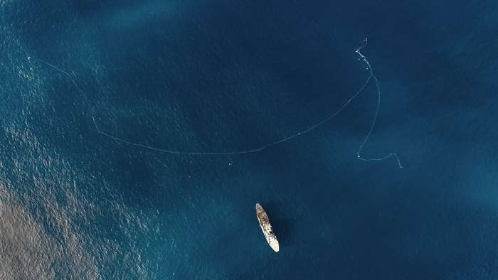 Driftnet curling around a 195-foot-long ship